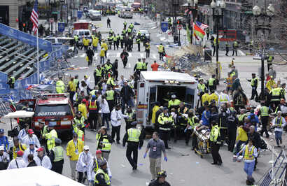 FILE This April 15, 2013 photo shows medical workers aiding injured people at the finish line of the 2013 Boston Marathon following an explosion.