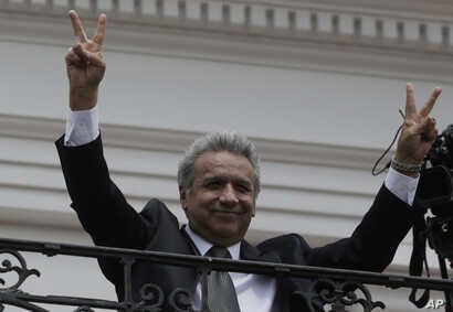 Ecuador's President Lenin Moreno flashes victory hands as he greets supporters from the Government Palace's balcony during the weekly Changing of the Guard, in Quito, Ecuador, Feb. 5, 2018.