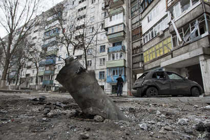 A piece of an exploded Grad missile is photographed outside an apartment building in Vostochniy, district of Mariupol, Eastern Ukraine, Jan. 25, 2015.