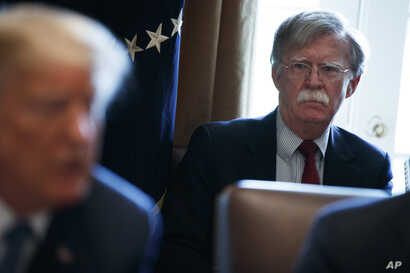 National security adviser John Bolton listens as President Donald Trump speaks during a cabinet meeting at the White House in Washington, April 9, 2018.