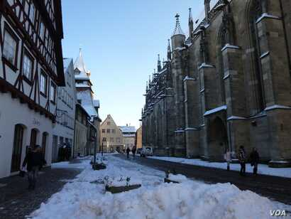 People are seen walking down a street in the historic downtown district of Schwaebisch Gmuend, Germany, Jan. 18, 2016. The town, as many others in Germany, is divided on how to handle the absorption of migrants and refugees. (H. Ridgwell/VOA)