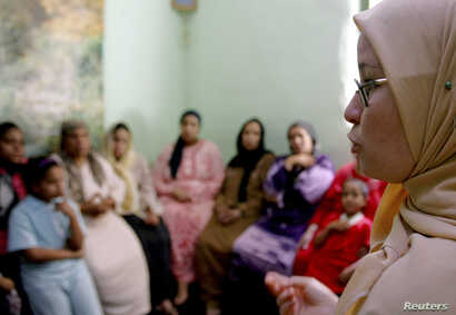 FILE - A counselor talks to a group of women to try to convince them that they should not have subject their daughters to female genital mutilation, in Minia, Egypt, June 13, 2006.
