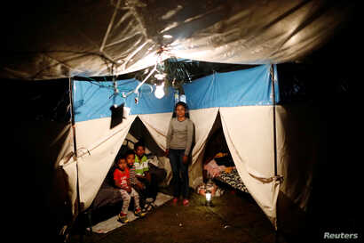 FILE - Veronica Dircio, 34, a housewife, stands with her sons in front of a tent in a neighbor's backyard after an earthquake in San Juan Pilcaya, at the epicenter zone, Mexico, Sept. 28, 2017.