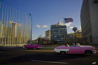 Tourists ride in classic American convertible cars past the United States embassy, right, in Havana, Cuba, Jan. 12, 2017.