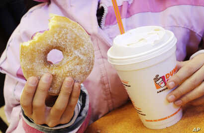 """FILE - A girl has a doughnut and a beverage in New York, Feb. 14, 2013. A new study finds more than half the calories consumed in the average American diet comes from """"ultra-processed"""" foods, including sugary drinks."""