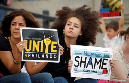 Two woman hold protest signs in support of Philando Castile during a rally on the capitol steps after a jury found St. Anthony Police Department officer Jeronimo Yanez not guilty of second-degree manslaughter in the death of Castile, in St. Paul, Min...