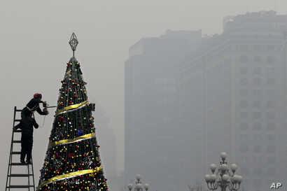 Workers install a Christmas tree on display outside a shopping mall in a heavy pollution haze in Beijing, Tuesday, Dec. 8, 2015.