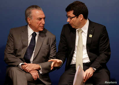 "Brazil's President Michel Temer speaks with Banco do Brasil CEO Paulo Rogerio Caffarelli, right, during a ceremony to launch the ""Simpler Undertakings"" Program in Brasilia, March 15, 2017."