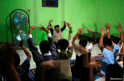 Recovering drug addicts and staff at a traditional rehabilitation center participate in physical activity during a prayer session led by Ustad Ahmad Ischsan Maulana in Purbalingga, Central Java, Indonesia, July 27, 2016. The center claims to have tre...