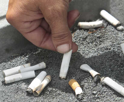 FILE -  A smoker snuffs out a cigarette at the Capitol in Sacramento, Calif., June 22, 2012.