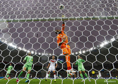 Algeria's goalkeeper Rais Mbolhi taps the ball away during the game between Germany and Algeria at the Beira Rio stadium in Porto Alegre, June 30, 2014.