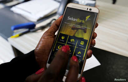 FILE - A customer uses her cell-phone to access the Sidian Bank mobile-app inside the banking hall at the Sidian Bank headquarters on the outskirts of Kenya's capital Nairobi.