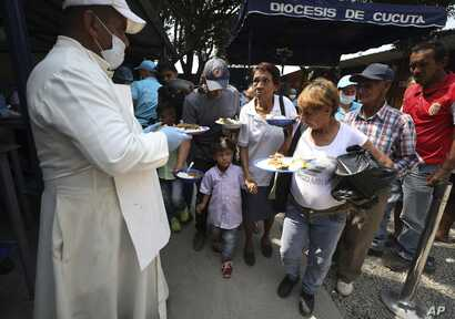 "Priest Richard Garcia  hands out free lunches to Venezuelan migrants at the ""Divina Providencia"" migrant shelter in La Parada, near Cucuta, on the border with Venezuela, Colombia, Monday, Feb. 11, 2019."