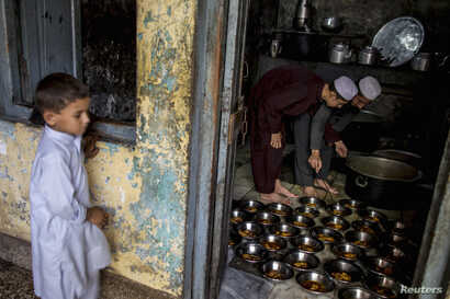 A boy stands while Pakistani religious students prepare food for their schoolmates at Darul Uloom Haqqania, an Islamic seminary and alma mater of several Taliban leaders, in Akora Khattak, Khyber Pakhtunkhwa province, Sept. 14, 2013.