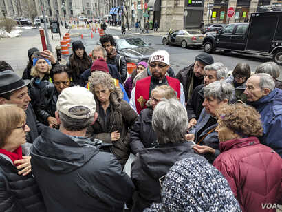 The Reverend Donna Schaper and immigrant-rights activists discuss next steps in support of Ravi Ragbir, a Trinidad-native activist who was detained during a routine check-in with immigration authorities. (R. Taylor/VOA)