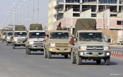 A convoy of Kurdish peshmerga fighters drive through Irbil after leaving a base in northern Iraq, on their way to Kobani, Syria, Oct. 28, 2014.
