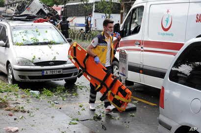 A Turkish medic rushes in to work at the explosion site after a bus carrying riot police official was struck by a bomb in Istanbul, Tuesday, June 7, 2016.