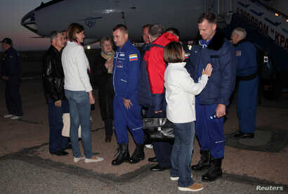 Russian cosmonaut Alexey Ovchinin, center, and U.S. astronaut Nick Hague, right front, meet with family members and acquaintances upon their arrival at Baikonur airport, Kazakhstan, Oct. 11, 2018.