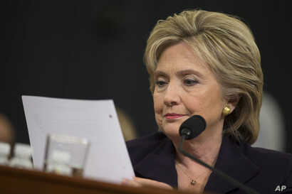 Democratic presidential candidate, former Secretary of State Hillary Rodham Clinton looks at an email sent by Ambassador Chris Stevens during her testimony before the House Benghazi Committee, Oct. 22, 2015, on Capitol Hill in Washington.