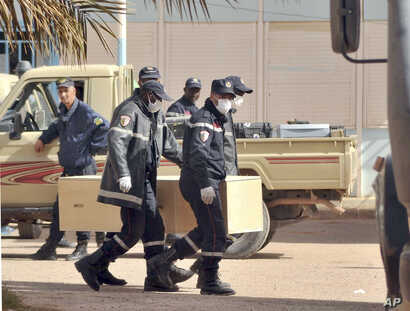 Algerian firemen carry a coffin containing a person killed during the gas facility hostage situation, at the morgue in Ain Amenas, Algeria, January 21, 2013.