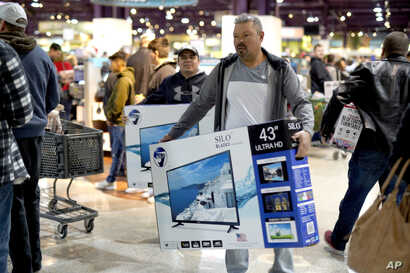 Black Friday shoppers carry their purchases at the Nebraska Furniture Mart store in Omaha, Neb., Nov. 23, 2018.