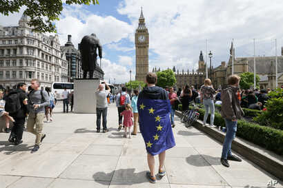 Wrapped in an EU flag, a demonstrator protests Britain's exit from the European Union at a rally in Parliament Square, London, June 25, 2016.