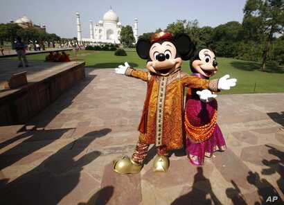 FILE - Walt Disney cartoon characters Mickey Mouse (L) and Minnie Mouse pose at the Taj Mahal in Agra, India, Oct. 30, 2008.