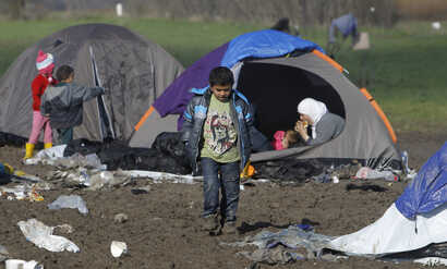 A boy walks through mud in an improvised camp on the border line between Macedonia and Serbia near northern Macedonian village of Tabanovce, Tuesday, March 8, 2016.