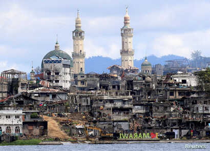 """FILE - A sign that reads """"I love Marawi"""" is seen in front of damaged houses, buildings and a mosque inside a war-torn Marawi city, southern Philippines, Oct. 26, 2017."""