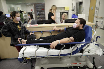 Donnie Cardenas, right, waits in an emergency room hallway alongside roommate Torrey Jewett, left, as he recovers from the flu at the Palomar Medical Center in Escondido, Calif., Jan. 10, 2018. The San Diego County resident said he was battling a hea...