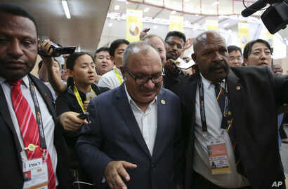 Papua New Guinea Prime Minister Peter O'Neill is escorted by security as he is pursued by reporters after reading his statement at the end of the APEC 2018 summit at Port Moresby, Papua New Guinea, Nov. 18, 2018.