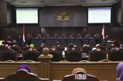 FILE - Judges read their verdict on the case of a petition seeking to make gay sex and sex outside marriage illegal during a hearing at the Constitutional Court in Jakarta, Indonesia, Thursday, Dec. 14, 2017.