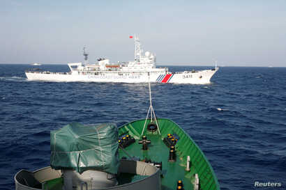 FILE - A ship (top) of the Chinese Coast Guard is seen near a ship of the Vietnam Marine Guard in the South China Sea, about 210 km (130 miles) off shore of Vietnam May 14, 2014.