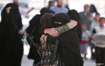 A woman embraces a Syria Democratic Forces (SDF) fighter after she was evacuated with others by the SDF from an Islamic State-controlled neighborhood of Manbij, in Aleppo Governorate, Syria, Aug. 12, 2016.