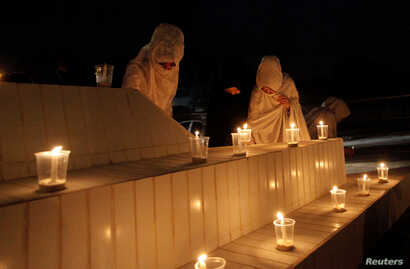 Women light candles during a candlelight vigil in honor of philanthropst Abdul Sattar Edhi in Quetta, Pakistan, July 9, 2016.