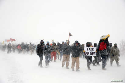 "Veterans join activists in a march just outside the Oceti Sakowin camp during a snow fall as ""water protectors"" continue to demonstrate against plans to pass the Dakota Access pipeline adjacent to the Standing Rock Indian Reservation, near Cannon Bal..."