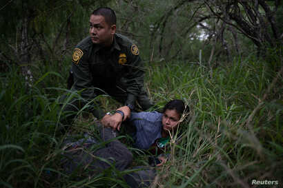 A border patrol agent apprehends a woman and a man after they were caught illegally crossing into the U.S. border from Mexico near McAllen, Texas, U.S., May 2, 2018.