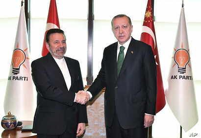 President of Turkey Recep Tayyip Erdogan, right, shakes hands with Mahmoud Vaezi, special envoy of Iranian President Hassan Rouhani, at his ruling party headquarters in Ankara, Turkey,  May 16, 2018.