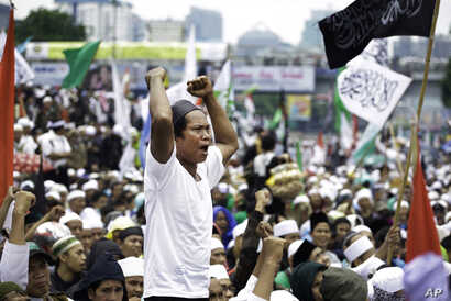 """FILE - A Muslim man shouts slogans during a rally against Jakarta's minority Christian Governor Basuki """"Ahok"""" Tjahaja Purnama demanding him to be sacked outside the parliament in Jakarta, Indonesia, Feb. 21, 2017."""