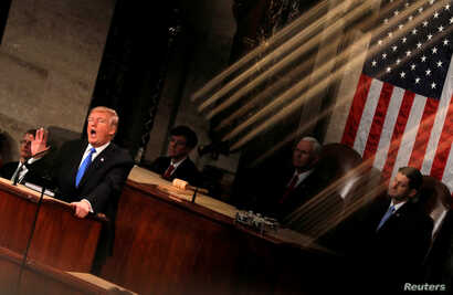 FILE - U.S. President Donald Trump and Vice President Mike Pence are seen behind the reflection of a House chamber railing as Trump delivers his State of the Union address to a joint session of the U.S. Congress on Capitol Hill in Washington, Jan. 30...