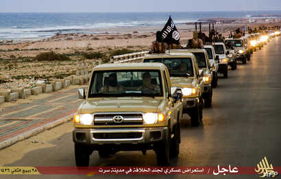 FILE - An image made available by propaganda Islamist media outlet Welayat Tarablos on February 18, 2015, allegedly shows members of the Islamic State (IS) militant group parading in a street in Libya's coastal city of Sirte, which lies 500 kilometre...
