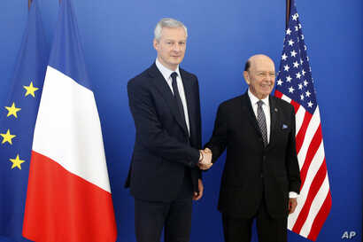 French Finance Minister Bruno Le Maire, left, welcomes US Secretary of Commerce Wilbur Ross prior to their meeting at French Economy Ministry in Paris, May 31, 2018.