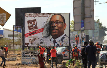 FILE - Opponents of Senegal's president Macky Sall vandalize a poster for the upcoming presidential elections in Thies, Senegal, Feb. 3, 2019.
