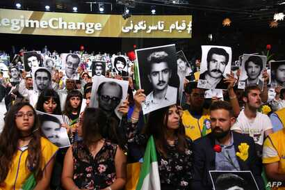 """People hold pictures of relatives killed by the Mohllas regime, during """"Free Iran 2018 - the Alternative"""" event, June 30, 2018 in Villepinte, north of Paris during the Iranian resistance national council (CNRI) annual meeting."""