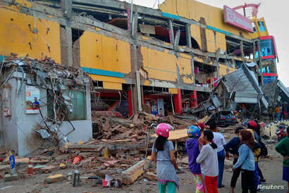 Residents stand in front of a damaged shopping mall after an earthquake hit Palu, Sulawesi Island, Indonesia, Sept. 29, 2018.