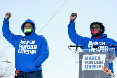 """Alex King, right, and D'Angelo McDade, left, both graduating seniors at North Lawndale College Prep High School in Chicago, raise their fists in the air as they arrive to speak during the """"March for Our Lives"""" rally in Washington, March 24, 2018. Bot..."""
