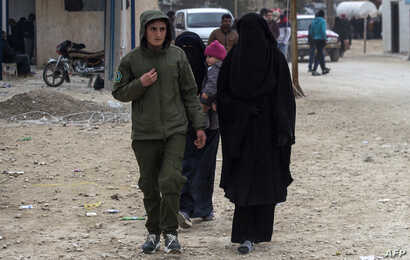FILE - A Kurdish female fighter, left, walks next to a woman, reportedly the wife of an Islamic State (IS) group fighter, at the Internally Displaced Persons (IDP) camp of al-Hol in al-Hasakeh governorate in northeastern Syria, Feb. 7, 2019.