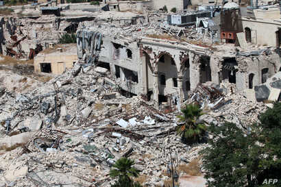 A picture taken on July 3, 2016 from the UNESCO-listed citadel shows the partially collapsed building of the famed Carlton Citadel Hotel (L), in the government-controlled side of the divided northern Syrian city of Aleppo.