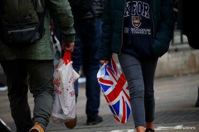 FILE - People carry shopping bags in London, Britain, Dec. 27, 2018.