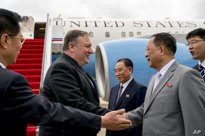 U.S. Secretary of State Mike Pompeo, second from left, is greeted by North Korean Director of the United Front Department Kim Yong Chol, center, and North Korean Foreign Minister Ri Yong Ho, second from right, as he arrives at Sunan International Air